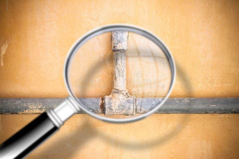 Controleer de oude waterpijpen - Conceptenbeeld dat door een vergrootglas wordt gezien stock afbeeldingen