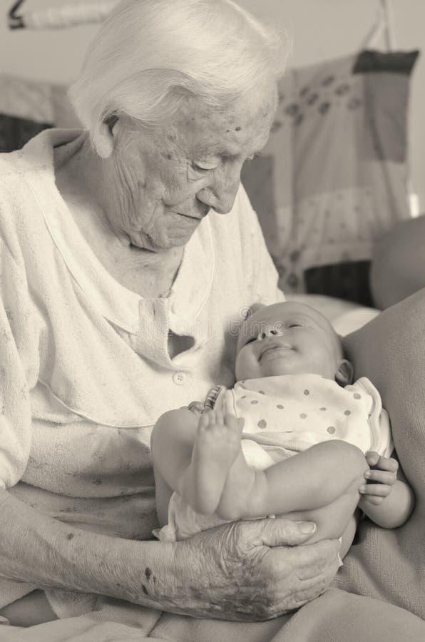 Controles de la bisabuela en brazos su grande-nieto fotos de archivo