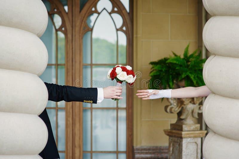 Controles del novio para el ramo de la boda de la novia foto de archivo