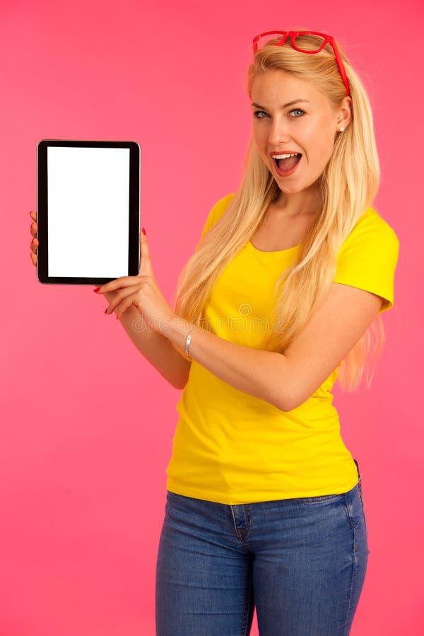 Controles hermosos tableta de la camiseta del amarillo del pecado de la mujer joven y Internet de las resacas sobre fondo rosado imágenes de archivo libres de regalías