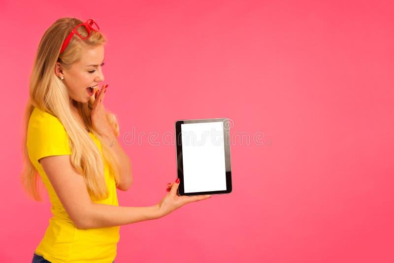 Controles hermosos tableta y resacas de la camiseta del amarillo del pecado de la mujer joven imagen de archivo libre de regalías