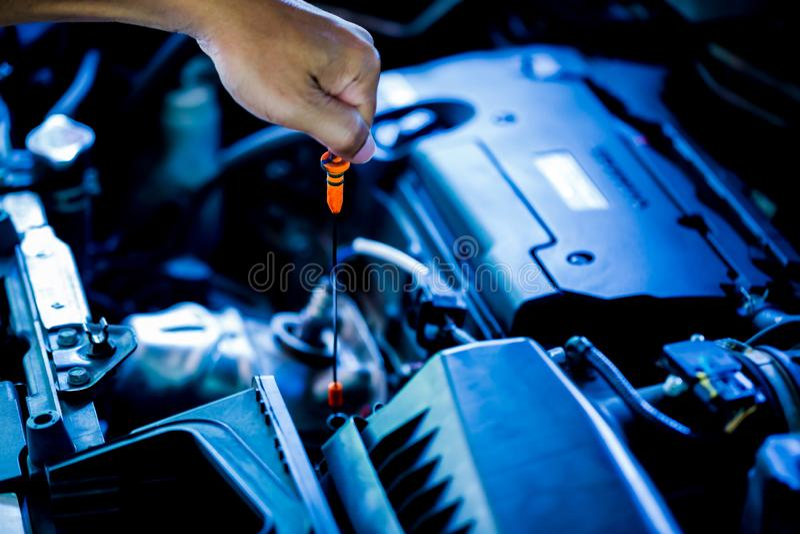 Controlli il livello di olio in motore di automobile Meccanico che controlla il motore o il veicolo di automobile immagini stock libere da diritti