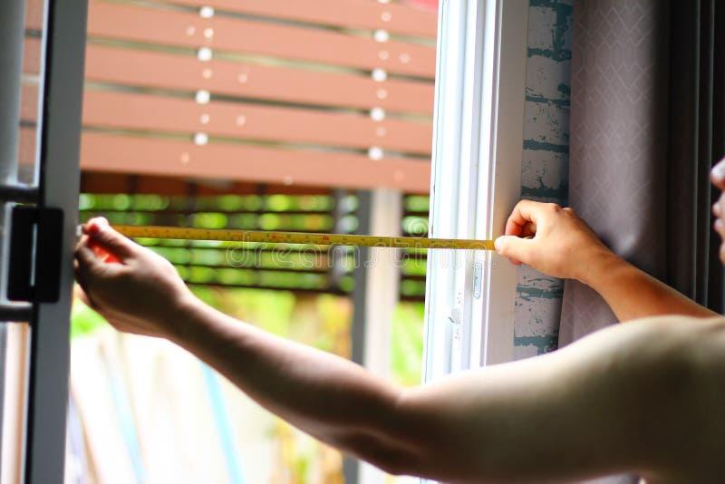 Controlli l'installazione della finestra con un cavo di misurazione fotografie stock libere da diritti