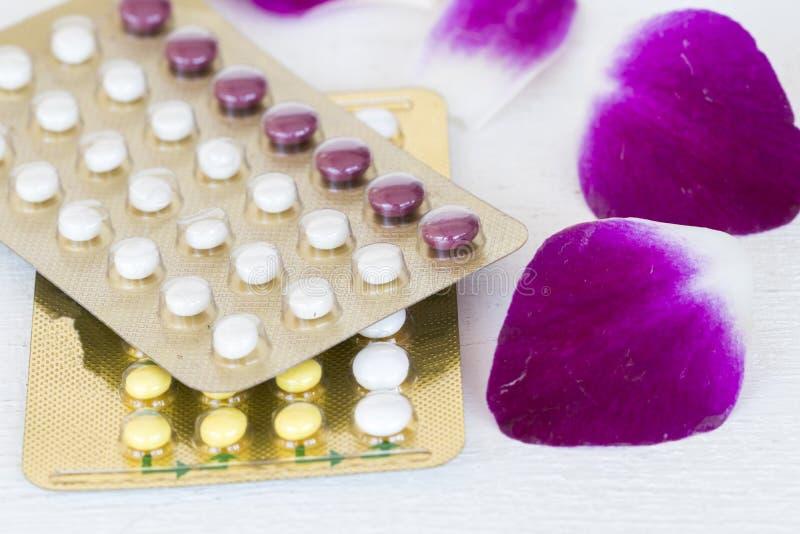 Controlli le pillole di tasso di natalità con floweer immagini stock
