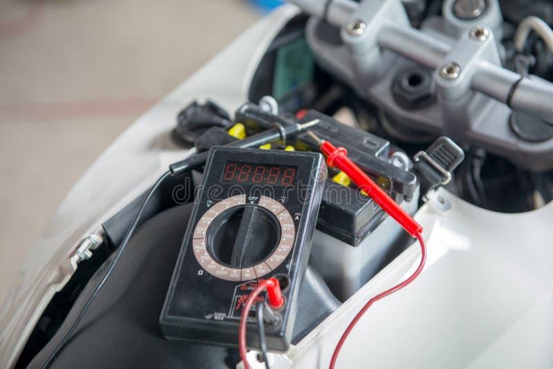 Controlli se la batteria del motociclo con il multimetro fotografie stock