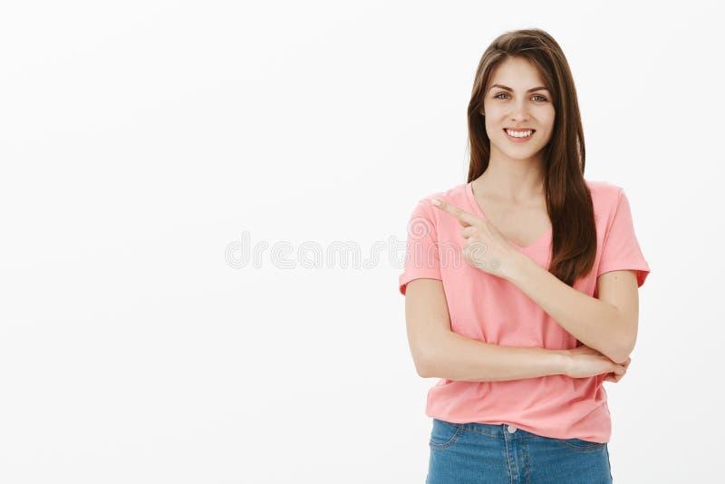 Controllilo fuori che non vi sareste rammaricato di Ritratto della femmina incantante ottimista in maglietta e jeans rosa, indica fotografia stock libera da diritti