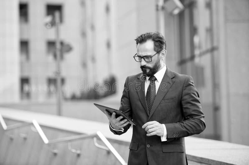 Controllo attraente dell'uomo d'affari o leggere compressa digitale fuori dell'edificio per uffici Il sociale comunica la tecnolo fotografia stock