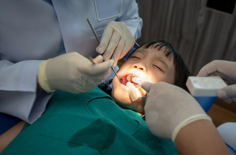 Controllo dei denti all'ufficio del ` s del dentista Denti d'esame delle ragazze del dentista nella sedia dei dentisti fotografie stock