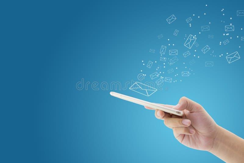 Controllo dell'uomo della tenuta della mano e messaggio di invio con il email in un telefono immagine stock libera da diritti