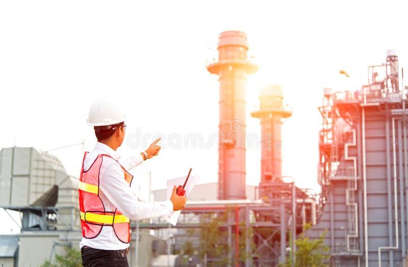 Controllo di sicurezza del lavoro della radio della tenuta dell'uomo dell'ingegnere all'industria energetica della centrale elett immagini stock libere da diritti