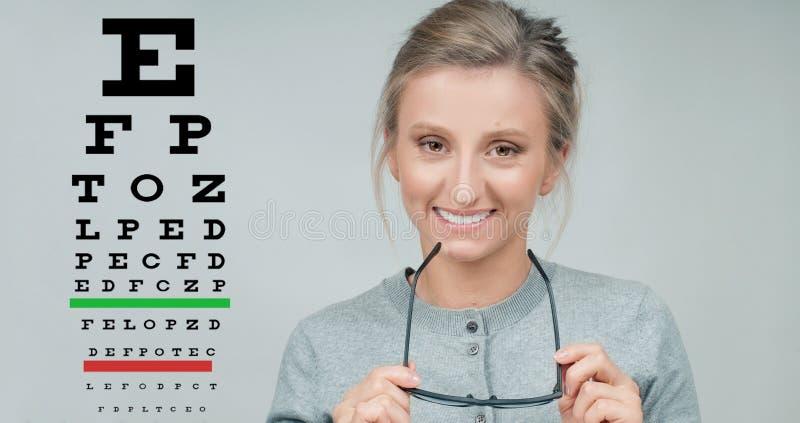 Controllo di vista Donna in vetri sui precedenti del grafico di prova dell'occhio fotografie stock