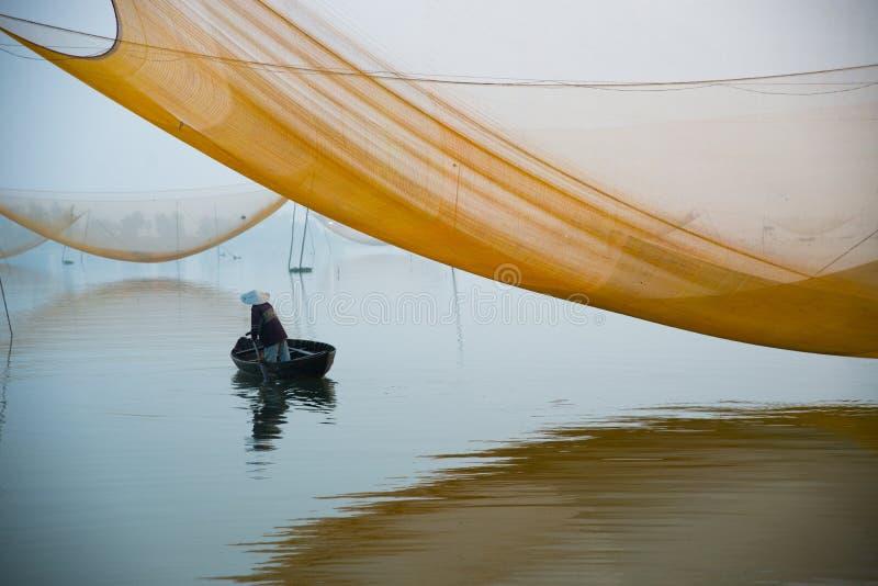 Controllo non identificato dell'uomo del pescatore le sue reti nel primo mattino sul fiume in Hoian, Vietnam immagine stock