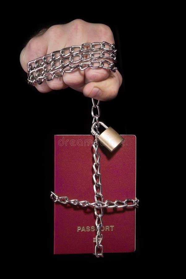Controllo sopra umanità Passaporto legato con una catena, su un fondo nero fotografia stock