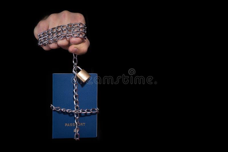 Controllo sopra umanità Passaporto legato con una catena, su un fondo nero immagini stock libere da diritti