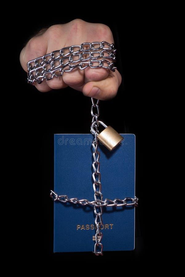 Controllo sopra umanità Passaporto legato con una catena, su un fondo nero immagine stock libera da diritti