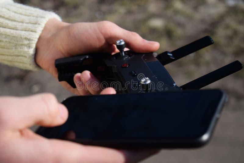 Controlo a distância e smartphone nas mãos masculinas Um homem que guarda um transmissor e que pilota alguns veículos Um zangão,  imagens de stock royalty free