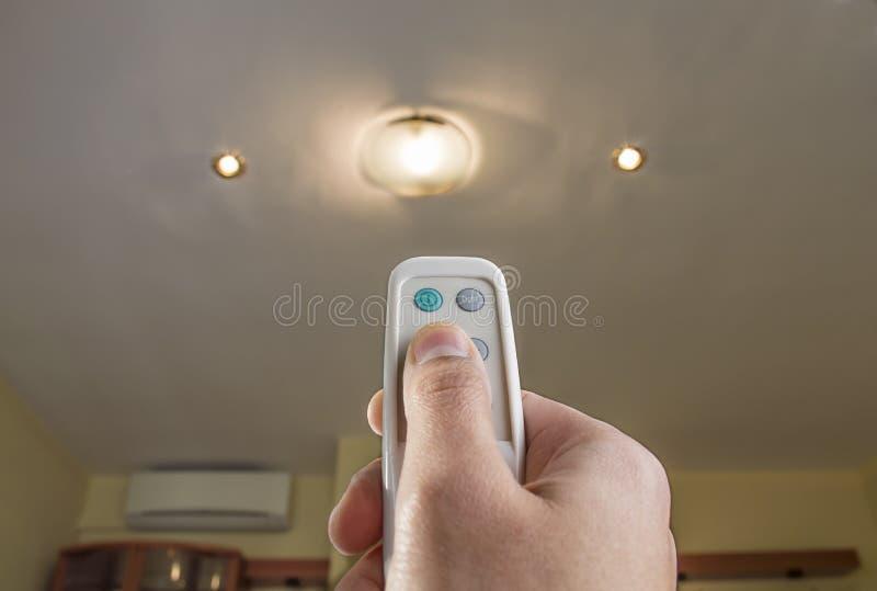 Controlo a distância que controla uma luz imagem de stock