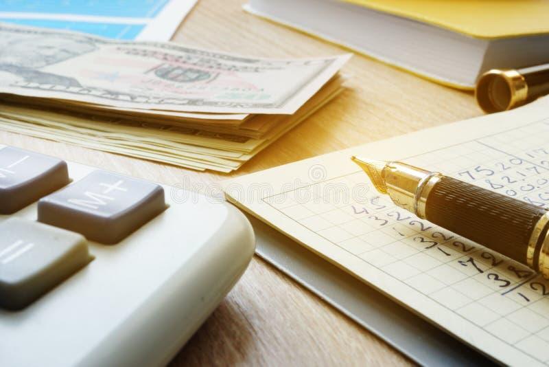 Controlo home do orçamento Notas de dólar, calculadora e nota com cálculos da finança fotografia de stock