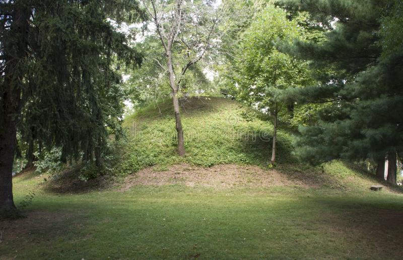 Conus Mound in Marietta, Ohio. The Conus burial Mound in Mound Cemetery, Marietta Ohio with trees framing and showing the full shape of the mound stock photography