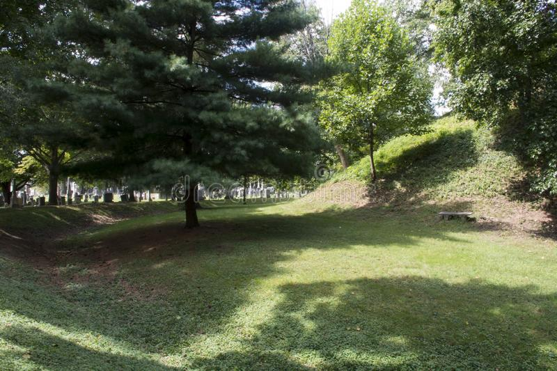 Conus Mound in Marietta, Ohio. The Conus burial Mound in Mound Cemetery, Marietta Ohio. This view shows the side of the mound and the mote that surrounds it stock photo