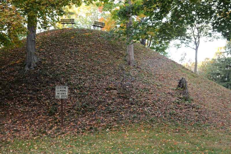 Conus. Is the name given this mound built by ancient native American i.dians known as Mound Builders. A burial mound situated in Marietta Ohio surrounded by a stock images
