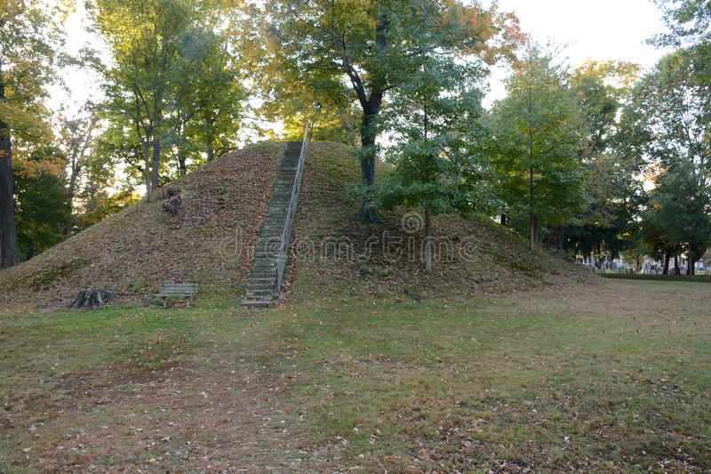Conus. Is the name given this mound built by ancient native American i.dians known as Mound Builders. A burial mound situated in Marietta Ohio surrounded by a stock photo