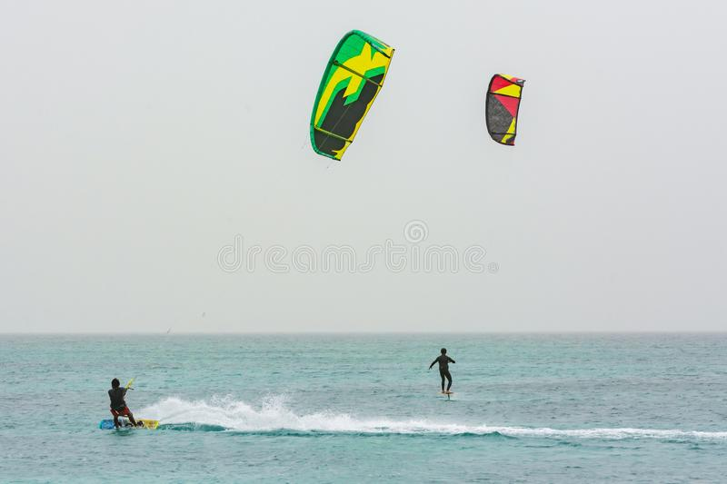 Kiteboarder and kite hydrofoiling man. Conventional kiteboarder and kite hydrofoiling man at Carlota beach, Boa Vista, Cape Verde, Africa stock photography