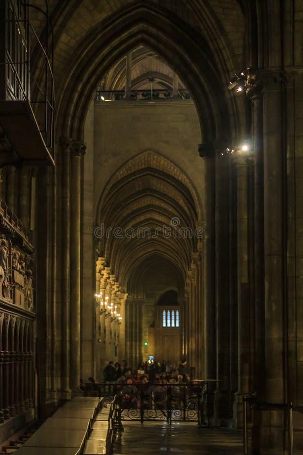 Convento gotico scuro con gli arché decorati il Notre Dame de Paris Cathedral con le finestre di vetro macchiato lungo la parete  immagine stock