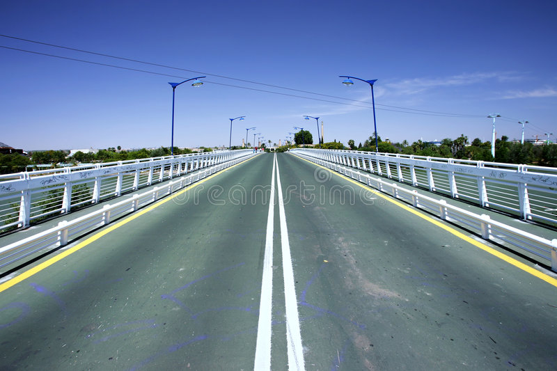 Converging lines of road on bridge stock images