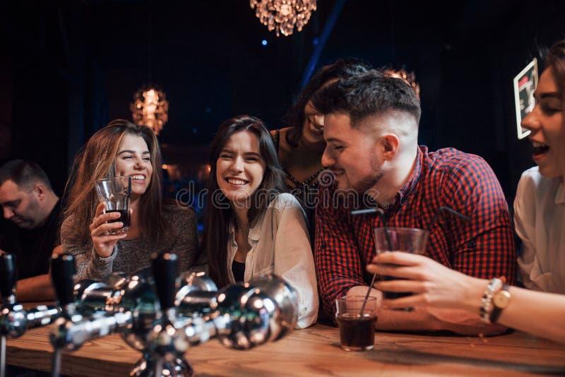 Conversação amigável Belos jovens se divertiram com álcool na boate imagens de stock