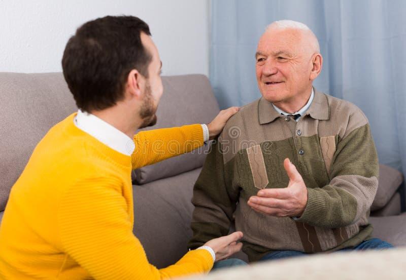 Conversação amigável velha do pai e do filho foto de stock