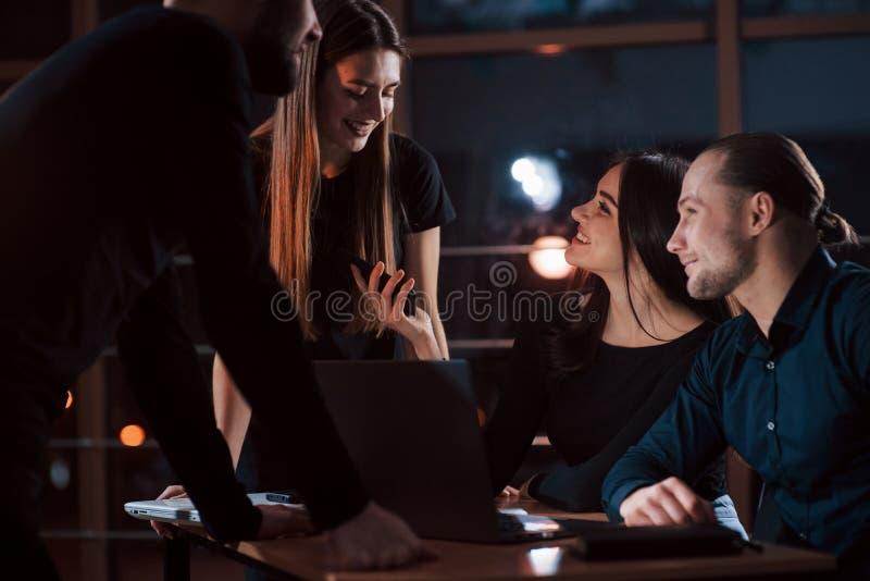 Conversação ativa Equipe de jovens empresários trabalha em seu projeto à noite no escritório fotos de stock royalty free