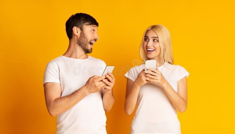 Conversação Em Casal Animado Segurando Smartphones Em Pé De Fundo Amarelo fotos de stock royalty free