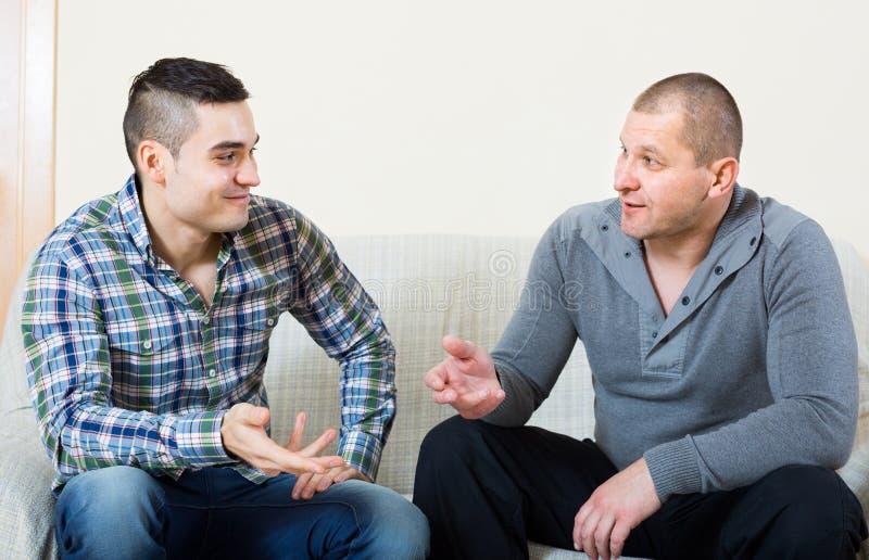 Conversação entre dois homens internos imagem de stock royalty free