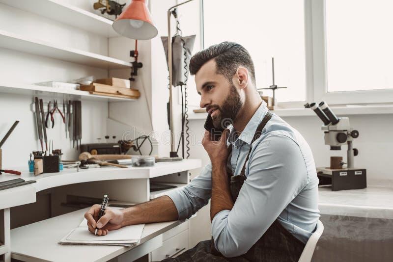 Conversação importante com cliente O joalheiro farpado novo está falando com o cliente pelo telefone e está fazendo uma anotação imagem de stock royalty free