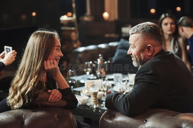 Conversação interessante e engraçada Amigos da família se divertindo em um belo luxo restaurante moderno fotografia de stock
