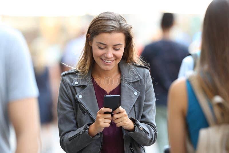 Conversa adolescente no telefone esperto que cerca por povos foto de stock