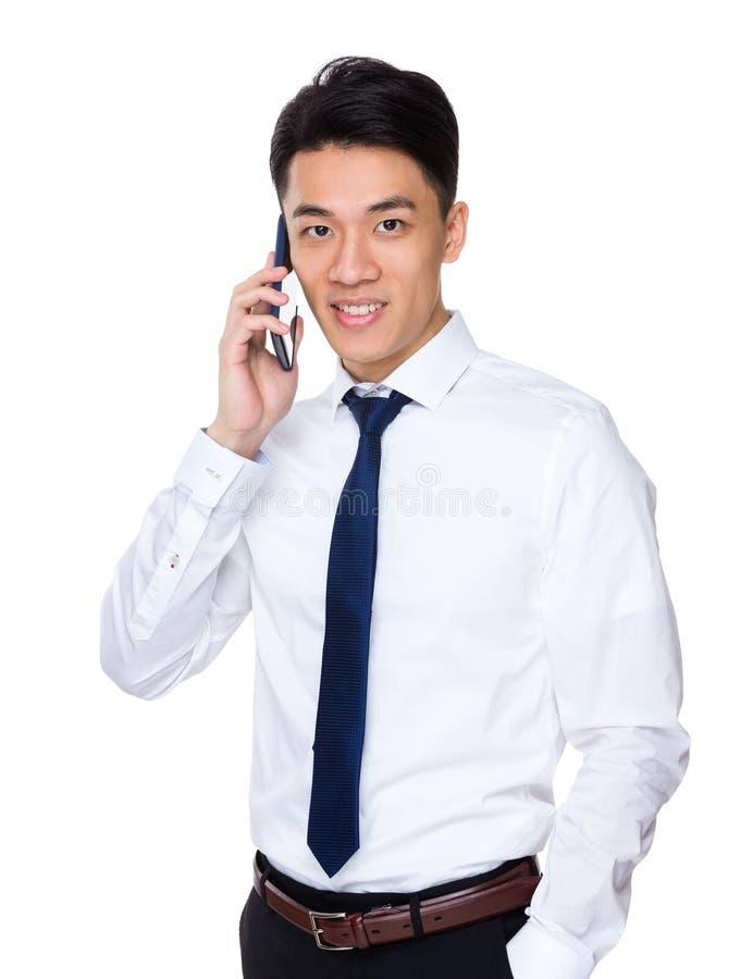 Conversa asiática do homem de negócios ao telefone celular imagem de stock