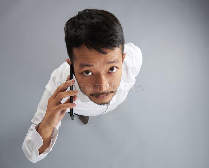 Conversa asiática do homem no smartphone foto de stock royalty free