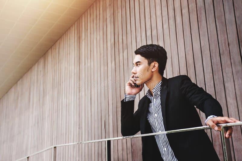 Conversa asiática nova do homem de negócios através do telefone esperto com seriamente a cara fotografia de stock royalty free