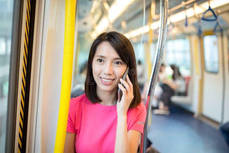Conversa da mulher ao telefone celular no trem fotografia de stock royalty free