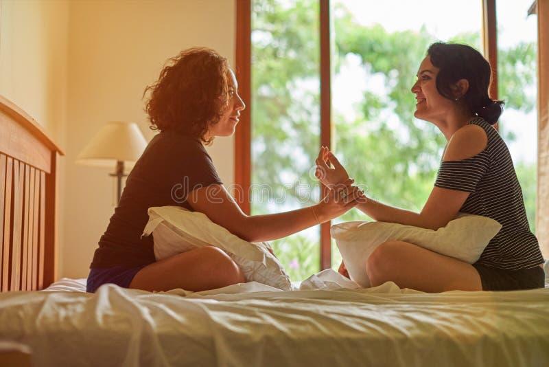 Conversa da mulher de dois hispânicos na cama imagem de stock