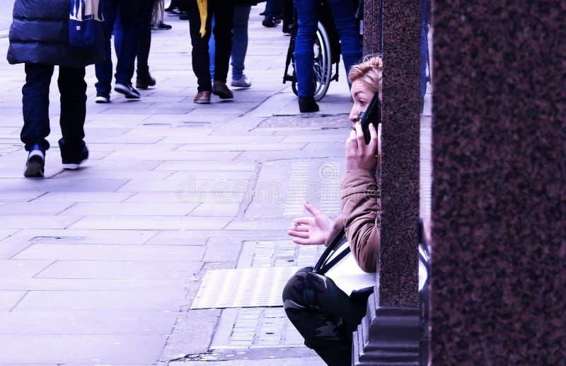 Conversa da rua Uma mulher senta-se em uma alcova de uma janela da loja que tem uma discussão caloroso em seu telefone esperto Av fotografia de stock royalty free