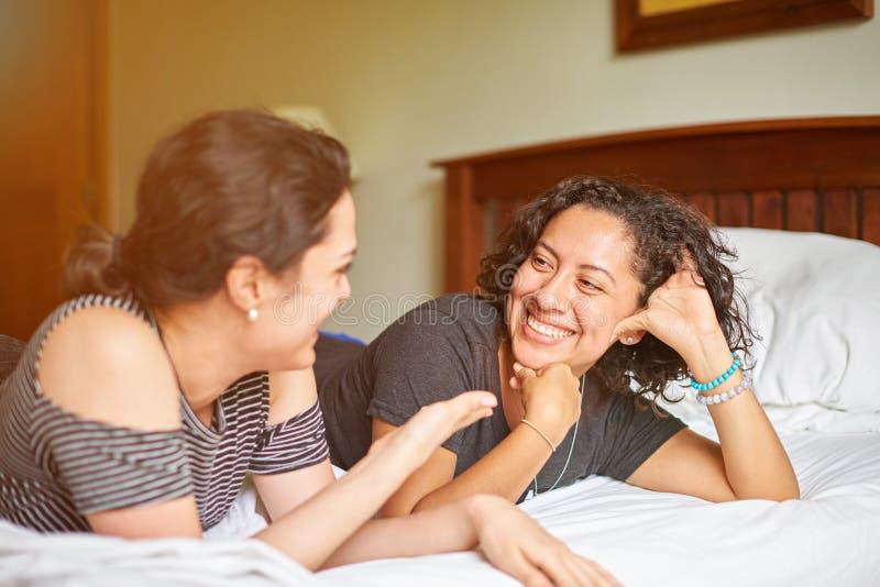 Conversa de duas jovens mulheres na cama fotos de stock