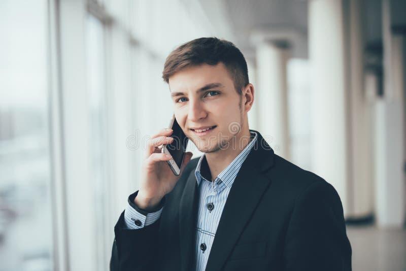 Conversa do homem de negócios ao telefone celular e olhar na câmera no escritório fotos de stock royalty free