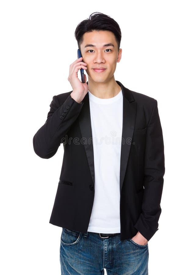 Conversa do homem novo ao telefone celular foto de stock