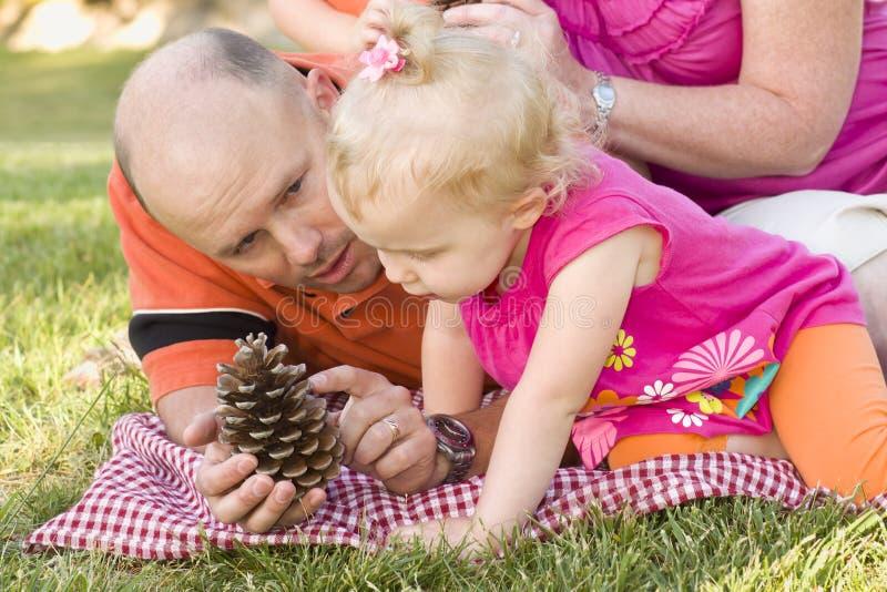 Conversa do pai e da filha sobre o cone do pinho no parque foto de stock