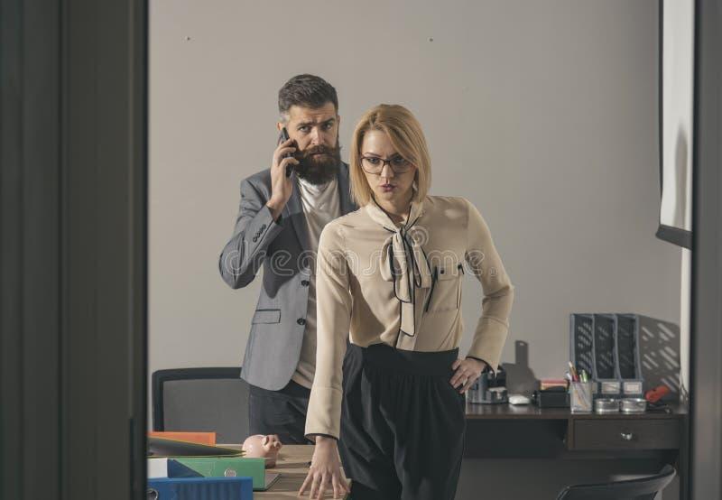 Conversa farpada do homem no smartphone no escritório Mulher sensual nos vidros e na roupa formal Homem de negócios e mulher de n foto de stock