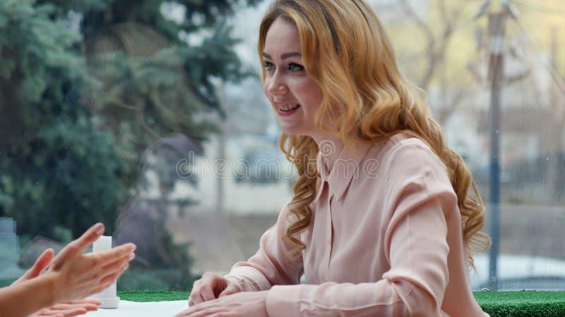 Conversa loura da menina de Positiva com seu amigo que fala em uma cafetaria foto de stock royalty free