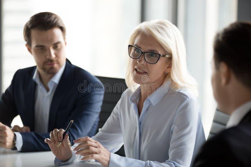 Conversa madura da mulher de neg?cios que negocia com os s?cios comerciais no encontro imagens de stock royalty free